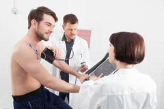 Physician taking a male patients blood pressure. During a routine medical check up as a nurse explains the readout on the monitor attached by sensors to his stock image