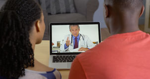 Physician talking with young black couple about medical issues Stock Photo