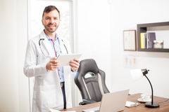 Physician using a tablet in his office. Friendly and attractive young physician looking at some patient's history on a tablet computer while standing in his Royalty Free Stock Images