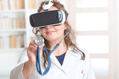 Physician using virtual reality headset. Medical doctor using virtual reality headset at the consulting room stock image