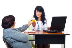 Physician woman offering apple to elderly Royalty Free Stock Photos