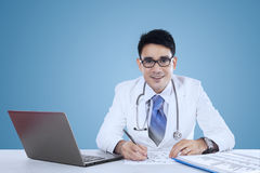 Physician working on desk over blue background Stock Photography