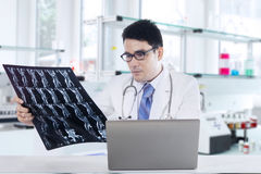 Physician with x-ray and laptop in laboratory Royalty Free Stock Images