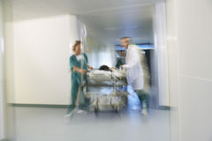 Physicians Moving Patient On Gurney Through Hospital Corridor Stock Photography