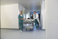 Physicians Moving Patient On Gurney Through Hospital Corridor Stock Photos