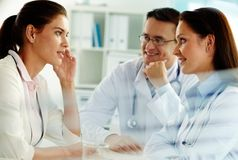 Physicians and patient. Portrait of confident practitioners consulting patient in hospital Stock Image