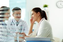 Physicians and patient. Portrait of confident practitioners consulting patient in hospital Stock Photos