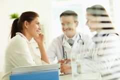 Physicians and patient. Portrait of confident practitioners consulting patient in hospital Stock Images