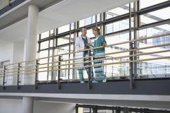 Physicians Talking On Balcony Stock Photo