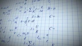 Physicmatematikformler som är skriftliga vid blåttpennan på anteckningsboksidan arkivfilmer
