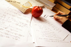 Physics. Hand writing physics formulas on a desk with physics calculations, books, an open book, a pencil and a set square Royalty Free Stock Photos