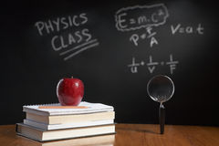 Physics class concept. With red apple on pile of books and magnifying glass with equation on blackboard stock photo