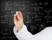 Physics diagrams and formulas. Research scientist writing physics diagrams and formulas with chalk on blackboard Royalty Free Stock Photos
