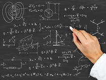 Physics diagrams and formulas. Research scientist writing physics diagrams and formulas with chalk on blackboard Stock Image