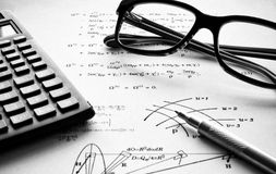 Physics exercises black and white. Physics formulas written on a white paper with pen in foreground, calculator and glasses in the background Royalty Free Stock Images
