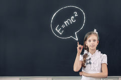 Physics formula. School girl at blackboard pointing at science formula with finger Royalty Free Stock Photos