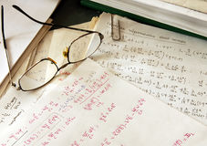Physics formulas. Glasses over physics formulas and calculations written on paper Stock Image