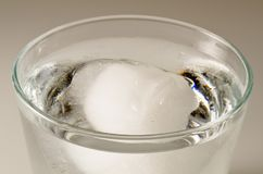 Physics. Ice cube floating over water. Stock Photography