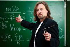 Physics professor. Against blackboard background royalty free stock image