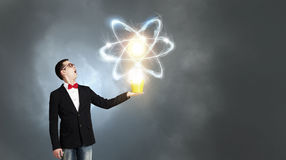 Physics science concept. Young man in black jacket with yellow bucket in hand Stock Photo