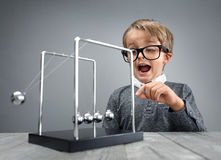 Physics and science education boy with Newton's cradle. Boy doing experiment with Newton's cradle physics concept for education, action and reaction or cause and Royalty Free Stock Photos