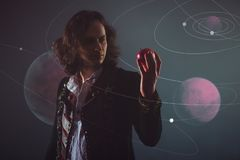 Physics the science of nature, the concept of studying the laws of nature. A young man in the image of Isaac Newton. With an Apple in hand, the concept of the royalty free stock photo