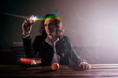 Physics the science of nature, the concept of studying the laws of nature. A young man in the image of Isaac Newton. Looks at the prism, the science of light stock photo