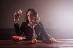 Physics the science of nature, the concept of studying the laws of nature. A young man in the image of Isaac Newton. Looks at the prism, the science of light royalty free stock photos