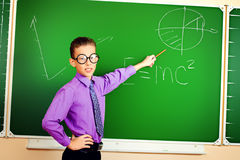 Physics. Smart schoolboy stands at the blackboard in the classroom. Education Royalty Free Stock Photo