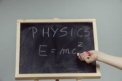Physics word and formula E=mc2 on chalkboard Royalty Free Stock Photography