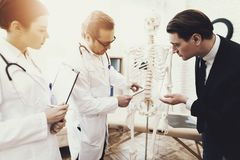 Physiiotherapist showing anatomical model of spine to patient in medical office. royalty free stock images