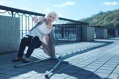 Physikalisch erschöpfte ältere Frau, die oben nachdem dem Fallen mit Krücken steht lizenzfreie stockfotografie