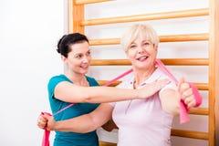 Physio hjälpande äldre kvinna under övning med maktmusikband a royaltyfria bilder