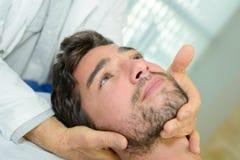 Physio terapeut som ger head behandling arkivbilder