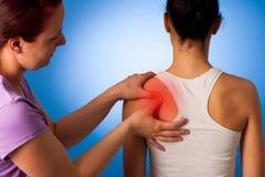 Physio terapeutportionkvinnan som den har, smärtar i henne tillbaka - som är tillbaka in Royaltyfri Bild