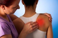 Physio terapeutportionkvinnan som den har, smärtar i henne tillbaka - som är tillbaka in Royaltyfri Fotografi
