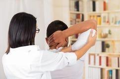 Physio- thérapeute féminin et homme vus par derrière, bras patient de aide de bout droit derrière la tête, fond trouble de cliniq Photo libre de droits