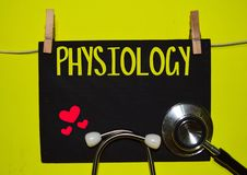 PHYSIOLOGY on top of yellow background. A stethoscope and blackboard with word PHYSIOLOGY on top of yellow background. Medical, health and education concepts royalty free stock photos