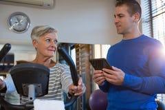 Physiothérapeute agissant l'un sur l'autre avec la femme supérieure tout en s'exerçant sur le vélo d'exercice Image stock