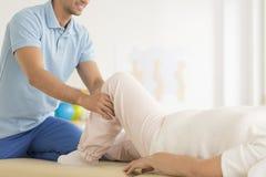 Physiothérapeute aidant dans le positionnement correct Photographie stock libre de droits