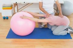Physiothérapeute aidant la femme supérieure avec la boule de yoga Photographie stock