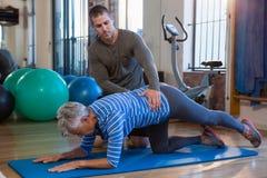 Physiothérapeute aidant la femme supérieure en exécutant l'exercice sur le tapis image stock