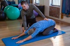 Physiothérapeute aidant la femme supérieure en exécutant l'exercice sur le tapis images libres de droits