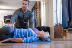 Physiothérapeute aidant la femme supérieure en exécutant l'exercice sur le tapis photographie stock