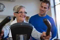 Physiothérapeute aidant la femme supérieure en exécutant l'exercice sur le vélo d'exercice image stock