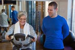 Physiothérapeute aidant la femme supérieure en exécutant l'exercice sur le vélo d'exercice photos stock