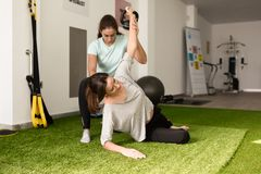 Physiothérapeute aidant la jeune femme caucasienne avec des WI d'exercice Image libre de droits
