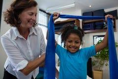 Physiothérapeute aidant la patiente de fille en exécutant l'exercice s'étendant de la bande de résistance photographie stock libre de droits