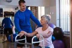 Physiothérapeute aidant la patiente supérieure de femme pour marcher avec le cadre de marche Photographie stock