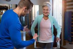 Physiothérapeute aidant le patient pour marcher avec le cadre de marche Photographie stock